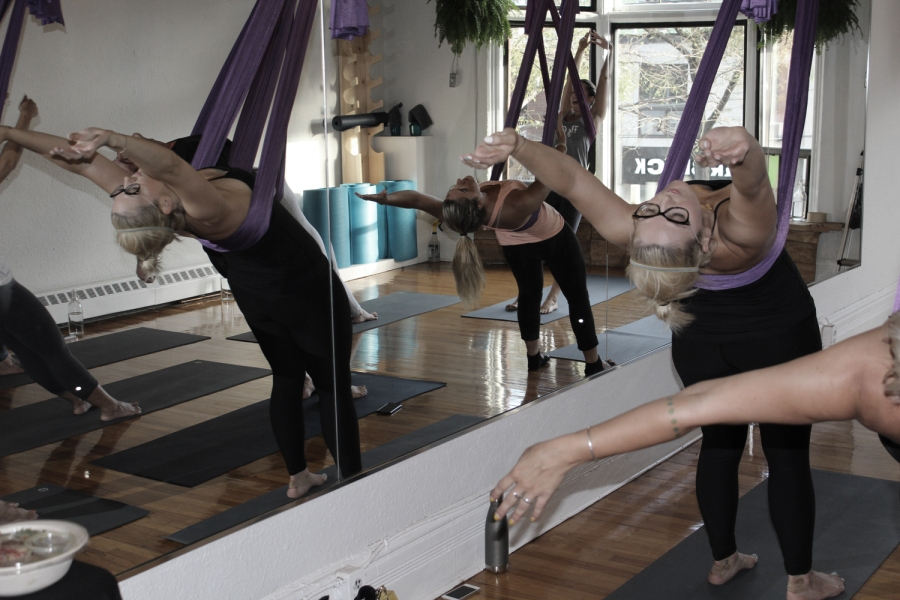 A bunch of people practicing aeriel yoga. They are leaning backward supported by purple silks suspended from a wooden beam.